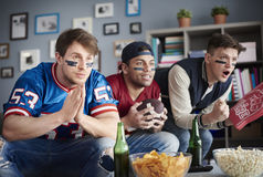 Watching football game. Front view of three men watching American football Stock Photos