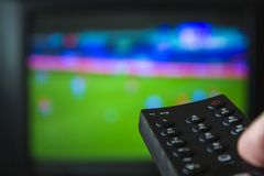 Watching football game and holding television remote control stock photo