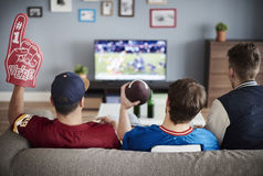 Watching football game. Three men with American football equipment Royalty Free Stock Photo