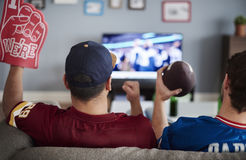 Watching football game. Two men with foam hand and baseball equipment Stock Photos