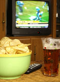 Watching Football on Television. Snacks on the coffee table for the big game Royalty Free Stock Photo