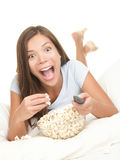 Watching fun movie - woman in bed. Woman watching funny movie on TV with shocked expression. Young beautiful female model eating popcorn having fun in bed Royalty Free Stock Photos
