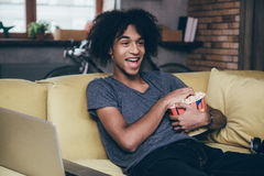 Watching funny movie. Cheerful young African man watching TV and holding bucket of popcorn while sitting on the couch at home Royalty Free Stock Photography