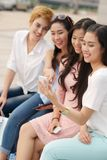 Watching funny video. Group of friends watching something funny on mobile phone Royalty Free Stock Image
