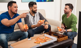 Watching a game and eating pizza. Three Hispanic male friends watching TV at home while eating pizza and drinking some beer Stock Photos