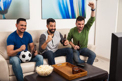 Watching the game with my friends. Group of Hispanic male friends watching a soccer game on TV and drinking some beer royalty free stock image