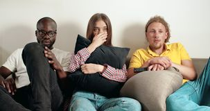 Watching Horror Film. Mixed race group of young frighntened people watching horror film sitting on grey sofa, indoors shot stock video footage