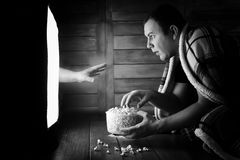 Watching a horror on TV black and white. A man watching a horror movie on TV black and whiter Royalty Free Stock Photo