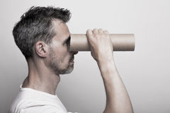 Watching the infinity. Man with a stubbly beard looks through a cardboard tube Royalty Free Stock Photo
