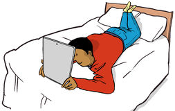 Watching ipad. Young man watching an ipad on a bed Stock Images