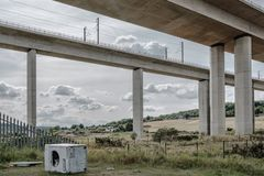 Illegally dumped washing machine seen under a motorway. The watching machine, seen on its side has been dumped on wasteland below a major motorway in the UK stock image