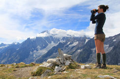 Watching Mont Blanc panorama. Young girl on top of the Mont Sapin with binocular , famous Mont Blanc panorama as background Stock Image