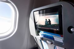 Watching movie on an airplane touch screen. Imaginary film. Watching movie on an airplane touch screen. Imaginary film playing on a video player in monitor stock photography