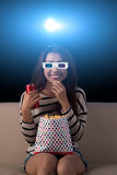 Watching movie. Smiling woman in 3D glasses eating popcorn and watching movie in the cinema Royalty Free Stock Image