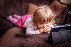 Watching movie on a tablet. Little girl laying on a sofa and watching cartoon on a small tablet Stock Photos