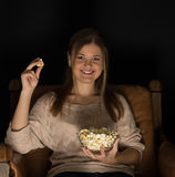 Watching movie. Young  woman, sitting in the dark room in the front of tv watching movie and eating popcorn, showing emotions Stock Image