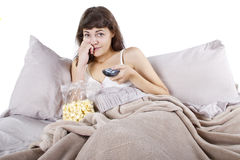 Watching Movies In Bed. Young teenager watching movies in bed with popcorn Royalty Free Stock Image
