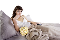 Watching Movies In Bed. Young teenager watching movies in bed with popcorn Stock Photos