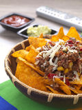Watching movies with a bowl of nachos. A bowl with spicy tortilla chips served with minced meat and cheese royalty free stock photo