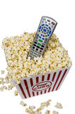 Watching Movies At Home Isolated. Great shot of a large tub of popcorn with a remote control in the center on white background Royalty Free Stock Images