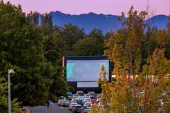 Watching movies in the open air in a car park in the city in the. Watching movies in the open air in a car park in the city in warm summer evening with mountains Royalty Free Stock Image