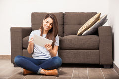 Watching my favorite tv show on a tablet. Cute young woman relaxing at home and watching a tv show on a tablet computer Stock Photography