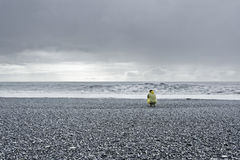 Watching the ocean. Man in a yellow rain coat kneeling down at the ocean stock photo
