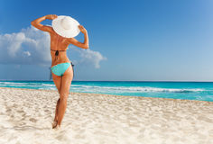 Watching the ocean. Beautiful woman on the beach in straw hat watching at the ocean Stock Photo