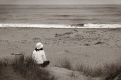 Watching The Ocean (bw). Young woman sitting at the beach looking over the ocean Stock Photos