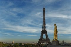 Watching the old Lady. Golden statue facing and watching the Eiffel tower on a blue and polluted sky Royalty Free Stock Image