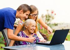 Watching Old Memories. Smiling family members watching old memories on the computer Royalty Free Stock Images