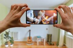 Free Watching Online Music Concert At Home Using A Mobile Phone. Guitar Close-up On The Screen Royalty Free Stock Images - 206319669