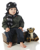 Watching for the Plane. An adorable toddler sitting on his suitcase while watching for an airplane in his old-time pilot's outfit, his pilot teddy bear by his Royalty Free Stock Image