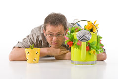 Watching Plants Grow. A man with a watering can lying down, watching his potted plant grow Stock Image