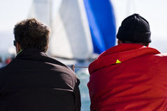 Watching Regatta. Two guys with sunglasses and hat on a boat watching Regatta / sailboat race - Barcolana - Trieste - Italy 2007 Royalty Free Stock Photo