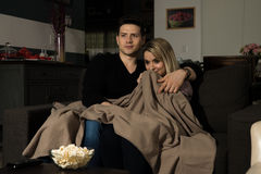 Watching a scary movie at night. Portrait of an attractive young couple huddled together and under a blanket while watching a scary movie at night Stock Images