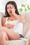 Watching a scary movie. Shocked young woman covering face with hands and watching movie while sitting on sofa Stock Photo