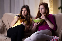 Watching scary movie. Young girls watching scary movie and eating popcorn Royalty Free Stock Photo