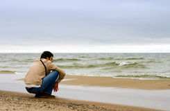 Watching the Sea. A man, sitting on the beach and watching the sea Royalty Free Stock Image