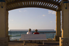 Watching the sea. Two old ladies seating on a bench watching the sea Stock Photos