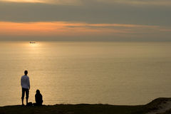 Couple of beach at sunset. Silhouetted couple on coastline looking at calm sea, sunset scene royalty free stock images