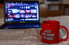 Watching series with a cup of tea. Just one more episode. Millennial concept. Watching series with a cup of tea. Inscription Just one more episode. Millennial stock photos
