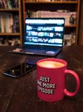 Watching series with a cup of tea on wood table with cellphone. Just one more episode. Millennial conceptn stock image