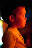 Watching show. Child watching show. Face profile in warm light from incandescent source Stock Images