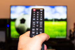 Watching soccer / football game on modern tv, with a close-up of. The remote control Royalty Free Stock Photo