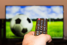 Watching soccer / football game on modern tv, with a close-up of. The remote control Stock Image