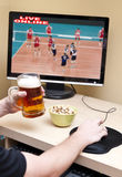 Watching sport online. Man drinking beer and watching online broadcast of a sport match Royalty Free Stock Photo