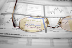 Watching the stocks. A color cut-out shot of a glasses over stock market graphs Royalty Free Stock Photos