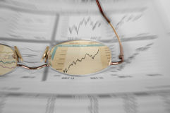 Watching the stocks. A color cut-out shot of a glasses over stock market graphs with extreme zoom effect Stock Photos