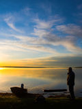Watching the Sunrise. A man stands along the shores of a lake during a beautiful sunrise stock photos